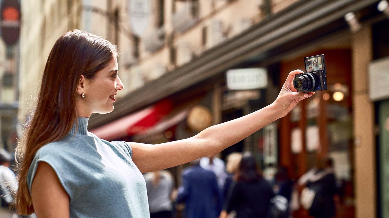A woman taking a selfie with her Sony's RX100 Mark VI